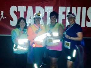 Patty MacMillan, right, celebrates with friends after completing the Into The Night 5 k Friday